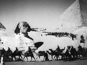 Travel dissolve: A caravan passes the Sphinx.